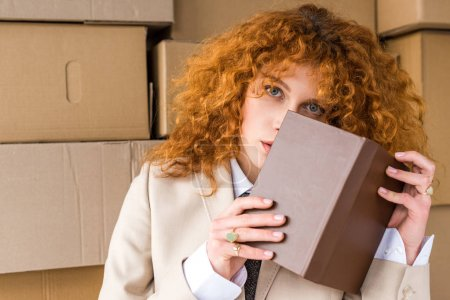Photo for Redhead woman covering face with book near cardboard boxes - Royalty Free Image