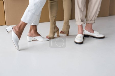 Photo for Cropped view of three girls standing in stylish footwear on white - Royalty Free Image