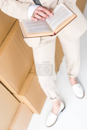overhead view of woman in formal wear standing with book near boxes on white