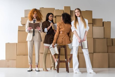 Photo for Attractive multicultural girls holding books near boxes on white - Royalty Free Image