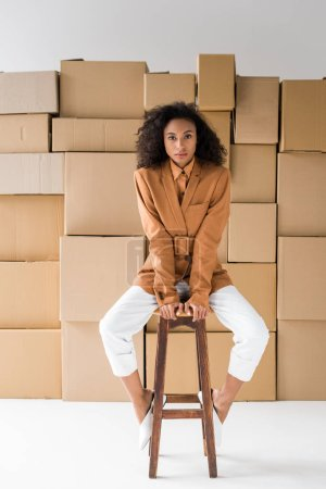 Photo for Attractive african american girl sitting on wooden chair and looking at camera on white - Royalty Free Image