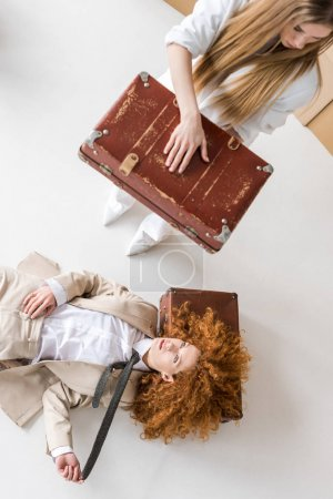 Photo for Top view of redhead woman lying near blonde girl standing with suitcase on white - Royalty Free Image