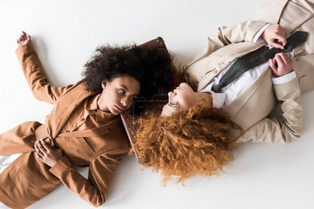 Photo for Top view of redhead girl lying near african american woman and suitcase on white - Royalty Free Image