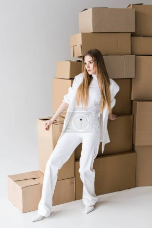 Photo for Attractive blonde young woman posing near carton boxes on white - Royalty Free Image