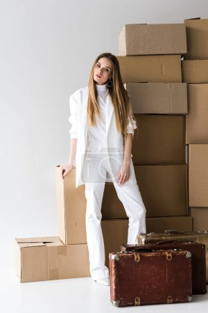 Photo for Attractive blonde young woman posing near suitcases and carton boxes on white - Royalty Free Image