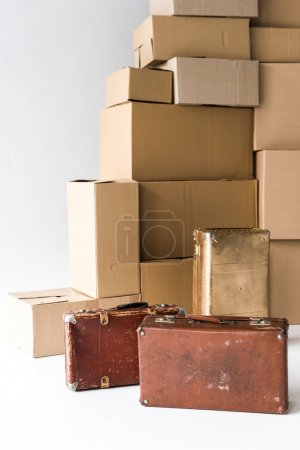Photo for Brown suitcases near stack of carton boxes on white - Royalty Free Image