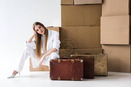 Foto de Atractiva mujer rubia posando cerca de maletas y cajas de cartón en blanco - Imagen libre de derechos