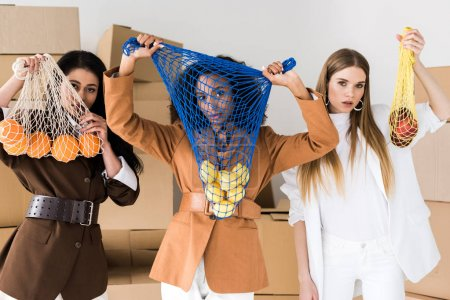 Photo for African american women covering faces while holding string bags with fruits near blonde girl on white - Royalty Free Image