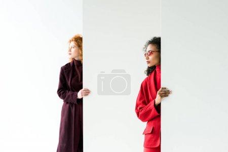 Photo pour Fille attirante de rousse et femme américaine africaine restant sur le blanc - image libre de droit