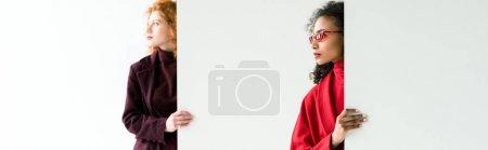 Photo pour Tir panoramique de la fille attirante de rousse et de la femme américaine africaine restant sur le blanc - image libre de droit
