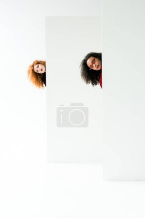 Photo for Curly redhead girl and beautiful african american woman looking at camera on white - Royalty Free Image