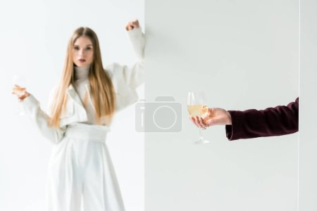 Photo for Cropped view of woman holding champagne glass near blonde girl on white - Royalty Free Image