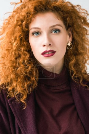 Photo for Attractive curly redhead woman looking at camera isolated on white - Royalty Free Image