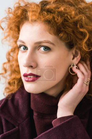 Photo for Close up of attractive curly redhead woman looking at camera and touching hair - Royalty Free Image