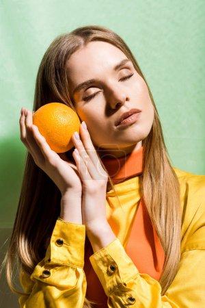 Photo pour Femme blonde attirante avec les yeux fermés retenant l'orange sur le vert - image libre de droit
