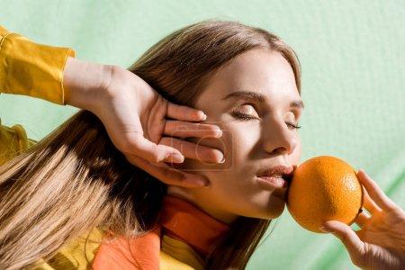 Photo pour Belle femme blonde avec les yeux fermés retenant l'orange sur le vert - image libre de droit