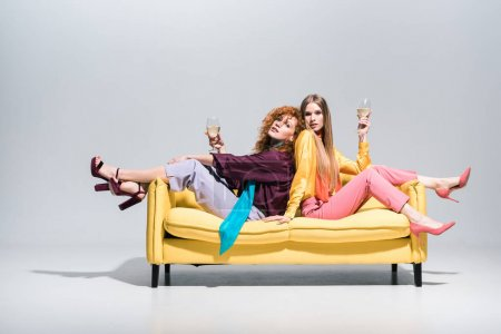 Photo for Attractive redhead girl and blonde young woman sitting on yellow sofa and holding champagne glasses on white - Royalty Free Image