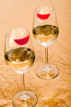 Photo for Red lipstick prints on champagne glasses with alcohol on orange - Royalty Free Image