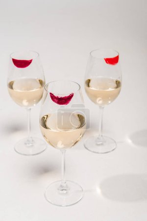 Photo for Lipstick prints on champagne glasses with alcohol on white - Royalty Free Image