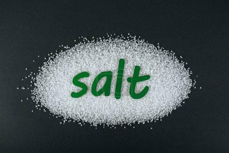Foto de Vista superior del papel verde cortado sal de la palabra en cristales de sal sobre fondo negro - Imagen libre de derechos
