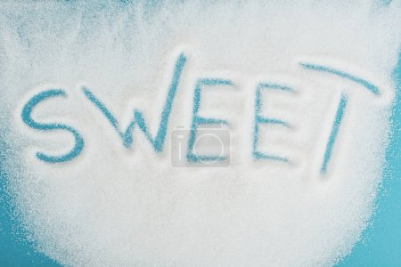 Photo for Top view of word sweet made on sprinkled white sugar crystals on blue surface - Royalty Free Image