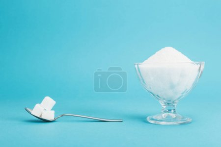 Photo for Glass bowl with granulated sugar and teaspoon with sugar cubes on blue background with copy space - Royalty Free Image