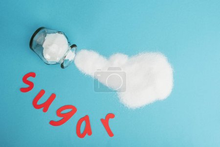 Photo for Top view of red paper cut word sugar near glass jar and sprinkled sugar crystals on blue background - Royalty Free Image