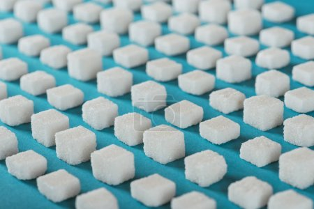 Photo for White sugar cubes arranged in rows on blue surface - Royalty Free Image