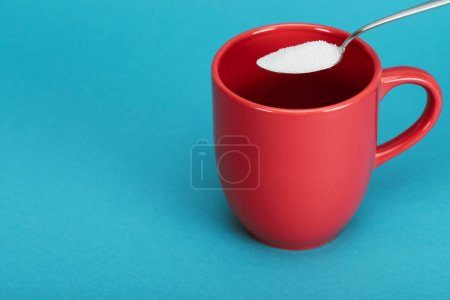 Photo for Teaspoonful of white granulated sugar near red cup on blue background - Royalty Free Image