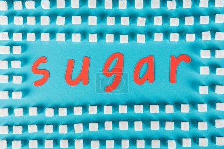 Photo pour Vue supérieure du sucre de mot coupé de papier rouge entouré par des cubes de sucre blanc sur la surface bleue - image libre de droit