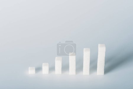 Photo for Stacks made of white sugar cubes on grey background with copy space - Royalty Free Image