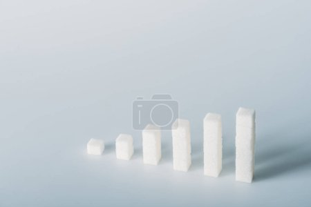 Photo for Stacks of white sugar cubes on grey background with copy space - Royalty Free Image