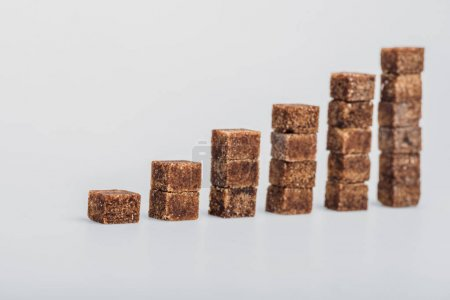Photo for Brown sugar cubes arranged in stacks on grey background - Royalty Free Image