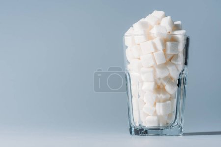 Photo for Glass full of refined white sugar cubes on grey background with copy space - Royalty Free Image