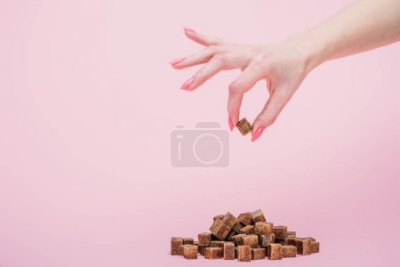 Photo for Cropped view woman with handful of white sugar cubes on isolated on pink - Royalty Free Image