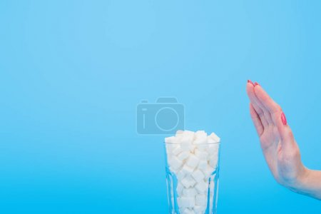 Photo for Cropped view of woman refusing from white sugar cubes in glass isolated on blue - Royalty Free Image