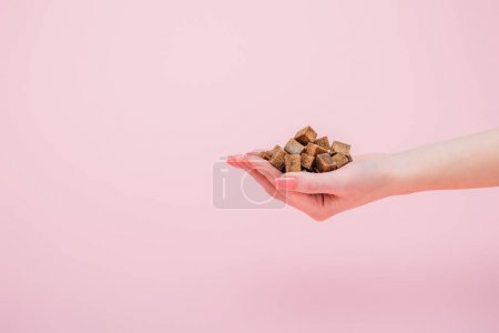 Photo for Cropped view of woman with handful of brown sugar cubes isolated on pink - Royalty Free Image