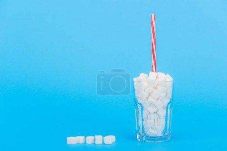 Photo pour Verre avec paille et cubes de sucre blanc sur fond bleu avec espace de copie - image libre de droit