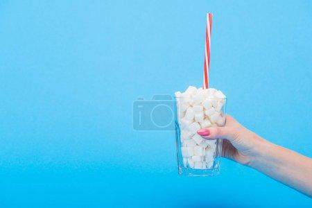 Photo pour Vue partielle de la femme tenant du verre avec de la paille et des cubes de sucre blanc isolés sur bleu - image libre de droit