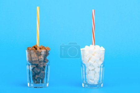 Photo for Glasses with straws and white and brown sugar cubes on blue background - Royalty Free Image