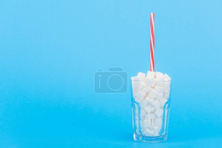 Photo for Glass with straw and white sugar cubes on blue background with copy space - Royalty Free Image