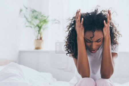 Photo for Exhausted african american woman suffering from headache in bedroom - Royalty Free Image