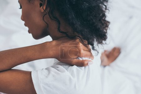 Photo for Selective focus of african american woman suffering from neck pain in bedroom - Royalty Free Image