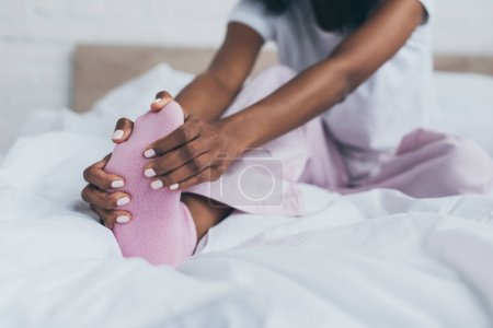 Photo for Cropped view of african american woman suffering from foot pain in bedroom - Royalty Free Image