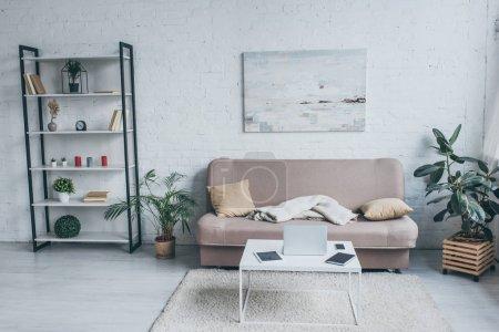 Foto de Spacious living room with sofa, rack, plants and table with digital devices - Imagen libre de derechos