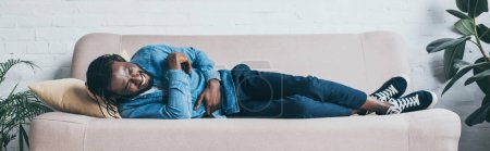 Photo for Panoramic shot of african american man suffering from abdominal pain while lying on sofa - Royalty Free Image
