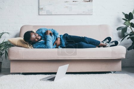 Photo for Young african american man suffering from stomach pain while lying on sofa near laptop on floor - Royalty Free Image