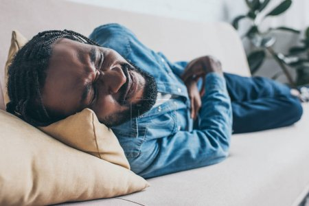 Photo for Selective focus of exhausted african american man lying on sofa and suffering from abdominal pain - Royalty Free Image