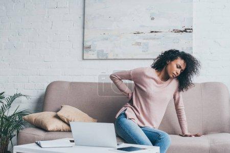 Photo pour Femme américaine africaine malheureuse souffrant de maux de dos tout en s'asseyant sur le sofa près de la table avec des dispositifs numériques - image libre de droit