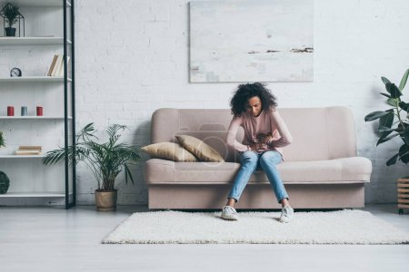 Photo for Young african american woman suffering from abdominal pain while sitting on sofa in living room - Royalty Free Image